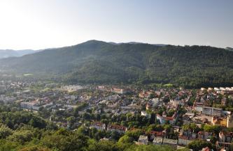 Blick von sehr hohem Standort auf die Häuserzeilen einer größeren Stadt, die sich bis zu einem bewaldeten Bergrücken im Hintergrund ausdehnen.