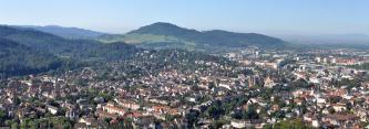 Panoramaansicht einer größeren Stadt mit längs und quer verlaufenden Häuserzeilen. Im Hintergrund erheben sich nach links ansteigende, bewaldete Hügel- und Bergketten.