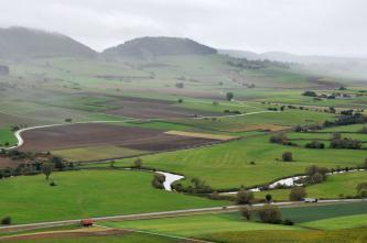 Von erhöhtem Standpunkt aus blickt man auf eine hügelige Landschaft mit Wiesen und Äckern. Links verlieren sich Berghänge im Dunst. Die Kuppen der Berge sind bewaldet. Im Vordergrund rechts schlängelt sich ein schmaler Fluss.