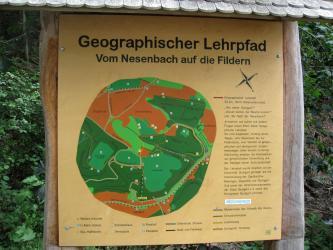 """Blick auf eine hölzerne Schautafel mit einer Karte, die den Verlauf des Geographischen Lehrpfades """"Vom Nesenbach auf die Fildern"""" anzeigt."""