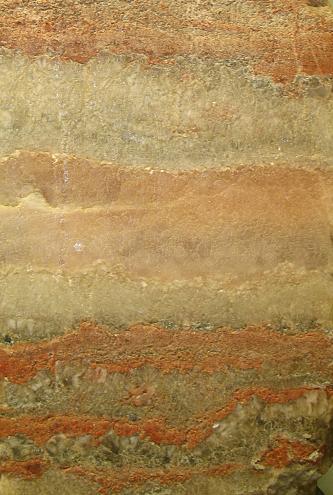 Das Bild zeigt eine Aufsicht auf ein glatt geschnittenes Gestein. Das mattgrün bis mattviolette Gestein wird oben und unten von roten Bändern durchzogen.