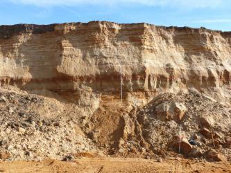 Blick auf die Abbauwand einer Sandgrube. In das hellbraune Material mischen sich waagrechte rötliche Streifen. Vor der Wand häufen sich Abraumhalden.