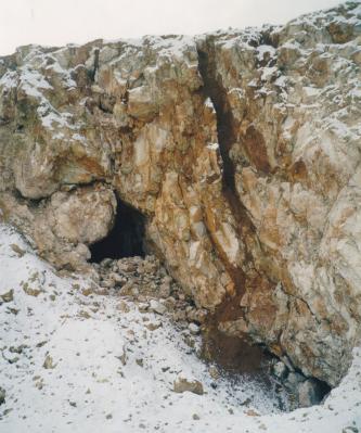 Man sieht eine zerklüftete, bräunlich graue Felswand mit einer senkrecht verlaufenden Nische rechts sowie einer kleinen Höhle links. Schnee bedeckt Teile der Felsen und den Hang davor.