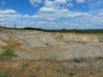 Panoramabild einer großen Kiesgrube, fotografiert vom Rand der Grube. Man sieht Bruchwände, Abraumhalden, Fahrwege, Bagger und Lastwagen.