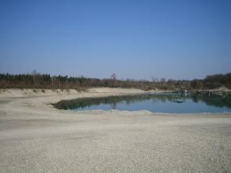 Blick auf eine dünenartige Landschaft mit Wald und einem See im Hintergrund. Auf dem See sind Förderanlagen zu erkennen. Im Vordergrund sind ausgedehnte Kiesflächen sowie Fahrwege.
