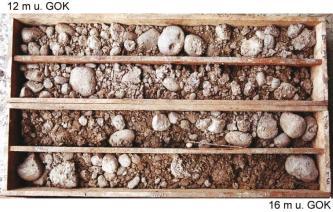 Das Foto zeigt Gesteinsmaterial, aufbewahrt in vier länglichen Kisten. Das Gestein ist weißlich grau bis rötlich und besteht aus teils rund geschliffenen, teils schartigen Bruchstücken.