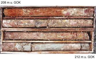 Das Foto zeigt vier in längliche Kisten gefüllte Bohrkerne. Das erbohrte Gesteins- und Erdmaterial ist unten weißlich grau, in der obersten Kiste rötlich braun. Die Oberfläche ist unten teils glatt, sonst grieselig.