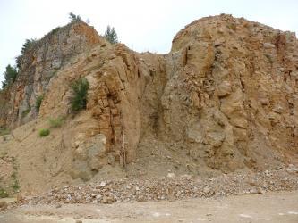 Zu sehen ist eine gelblich braune Steinwand in deren Mitte sich eine Spalte mit leicht dunklerem Material vom restlichen Gestein farblich absetzt. An dieser Stelle ist die Oberfläche auch etwas eingesackt.