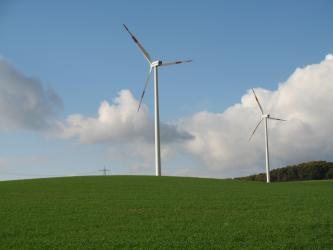 Das Bild zeigt einen flachwelligen grünen Hügel, auf dem zwei Windräder errichtet worden sind.