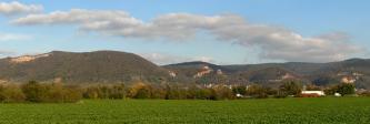 Panoramablick auf mehrere unterschiedlich hohe, bewaldete Berge. Teilweise sind Felsen sichtbar, links oben auch ein Steinbruch. Im Vordergrund sind Waldstreifen, eine Schnellstraße sowie flache Wiesen und Felder zu sehen.