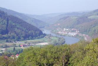 Blick von erhöhtem Standort auf eine Flussschlinge, von der allerdings nur der hintere Teil sichtbar ist. Vorne verdecken Bäume die Sicht. Links und rechts des Flusses erheben sich bewaldete Berge. Der Uferbereich links ist flach und besiedelt.