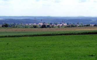 Blick über grüne Wiesen und Felder auf eine tiefer liegende Ortschaft mit Kirchtürmen. Im Hintergrund dehnen sich flache bewaldete Höhenzüge aus.