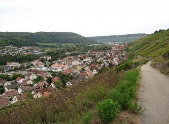 Blick von einem höher gelegenen Weg auf Rebhänge rechts oben sowie eine Siedlung links unten im Tal. Im Hintergrund bewaldete Höhen.
