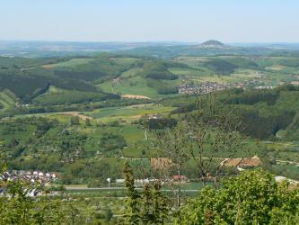 Blick aus großer Höhe auf eine hügelige Mosaiklandschaft aus Siedlungen, begrünten Ackerflächen und Waldstücken. Am Horizont erhebt sich eine Vulkankuppe in den blauen Himmel.