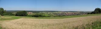 Panoramablick über ein Getreidefeld auf tiefer liegende, ovale Flächen mit Landwirtschaft und Siedlungen. An den Rändern und im Hintergrund Wald.