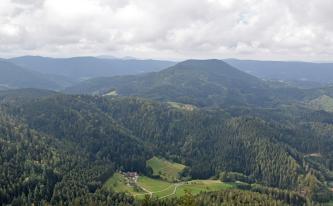 Blick aus großer Höhe auf einen leicht nach rechts abfallenden bewaldeten Bergrücken. Dahinter erhebt sich rechts ein abgeflachter Berg sowie weitere Berge, die Ketten bilden. Am vorderen Berg sowie mittig befinden sich baumlose Flächen mit Häusern.