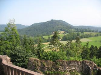 Blick über eine steinerne Brüstung auf Mauern, Bäume, nach rechts aufsteigende Hügel mit Wiesen und Feldern sowie einen bewaldeten Berg im Bildhintergrund.