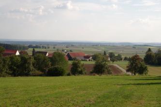 Blick über eine zum Betrachter hin aufsteigende Wiese über eine leicht wellige, flach abgestufte Landschaft, die bis zum Horizont reicht. Im Mittelgrund Bäume, ein dunkelbrauner Acker sowie einzelne Häuser einer Ortschaft.