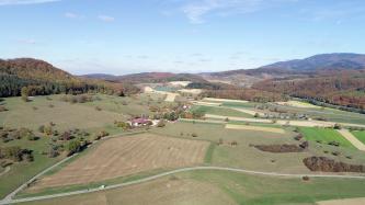 Von hoch oben blickt man auf eine hügelige Landschaft mit Straßen, Äckern, Wiesen und Baumgruppen. Im Hintergrund schließen sich größere Waldflächen und bewaldete Berge an.