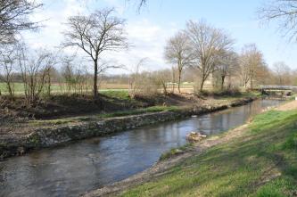 Blick auf einen schmalen, geraden Fluss mit von Bäumen gesäumten Uferdämmen. Im Hintergrund sind flache Äcker erkennbar.