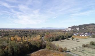 Unter einem Himmel mit Schleierwolken breitet sich eine flache Landschaft mit weiten Waldflächen aus. Im Vordergrund rechts schließen sich Äcker an, rechts hinten erhebt sich ein Hang mit Felsen und Wald. In der Ferne sind noch schwach Berge erkennbar.