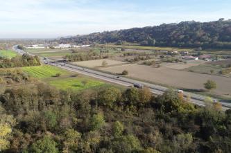 Im Vordergrund ist ein kleiner Wald, durch die Bildmitte verläuft in einem Bogen eine Autobahn. Rechts und links davon sind landwirtschaftlich genutzte Felder. Im Hintergrund ist ein bewaldeter Hügel