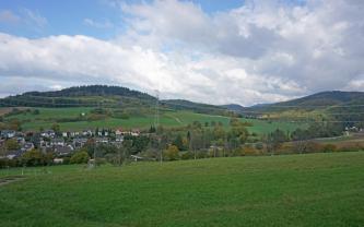 Zwischen grünen Hügeln im Vordergrund und teils grünen, teils bewaldeten Hügeln und Bergen im Hintergrund liegt ein schmales, links besiedeltes Tal.