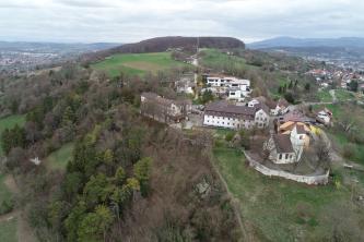 Aus großer Höhe blickt man über einen links und hinten bewaldeten Berg. Rechts verteilen sich einige Häuser und eine kleine Kirche. Im Hintergrund sind ausgedehnte Siedlungsflächen sowie Bergketten erkennbar.