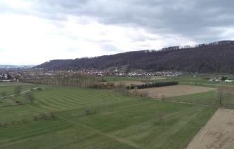 Blick von oben auf flache Wiesen und Äcker, durchkreuzt von Wegen, einem von Bäumen gesäumten Graben sowie einer Straße. Links und mittig folgt eine Siedlung, nach rechts erhebt sich ein bewaldeter, langgezogener Bergrücken.