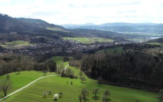 Aus großer Höhe blickt man über ein im Vordergrund hügeliges, von Wäldern eingerahmtes Tal. In der Bildmitte erstreckt sich eine größere Siedlung. Links ist ein bewaldeter Hang, rechts bewaldete Bergketten zu sehen.