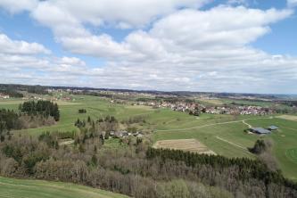 Blick von oben auf eine weit ausgebreitete, flache Landschaft mit Äckern, Wiesen, Wäldern und Siedlungen unter wolkigem Himmel.
