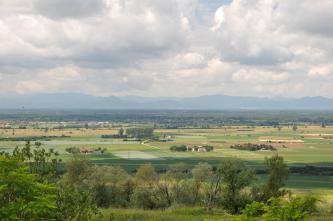 Unter einem sehr wolkigen Himmel breitet sich eine flache Landschaft mit Wiesen und Feldern sowie einzelnen Höfen aus. Im fernen Dunst erhebt sich eine Bergkette. Im Vordergrund steigt ein Wiesenhang mit Bäumen und Sträuchern auf.
