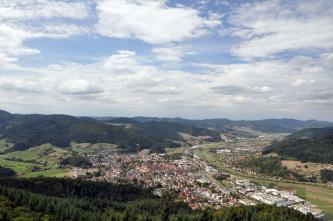 Das Bild zeigt einen weiten Blick auf eine zwischen bewaldeten Bergen und einem Fluss gelegene größere Ansiedlung.