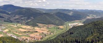 Von erhöhtem Standpunkt aus blickt man auf weite Nadelwälder rechts und eine aus landwirtschaftlichen Nutzflächen und Siedlungen bestehende Talebene links, durch die ein begradigter Fluss fließt. Dahinter folgt eine bewaldete Berglandschaft.