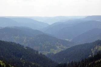 Ein aus großer Höhe gemachtes Bild, das mehrere hintereinander gestaffelte, bewaldete Berge zeigt.