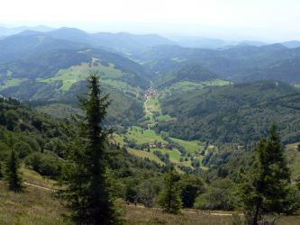Aus großer Höhe blickt man in ein kleines, schmales Tal mit einer Siedlung am Ende. Links und rechts des Tales sowie im Vorder- und Hintergrund erheben sich steile, teilweise bewaldete Hügel und Berge.
