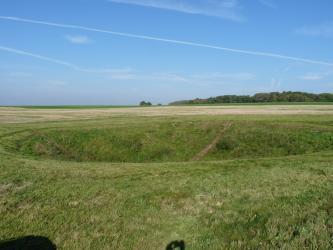 Inmitten einer großen Grünlandfläche öffnet sich eine ovale, dunkler gefärbte Vertiefung. Dahinter folgen Ackerflächen, weiteres Grünland sowie rechts ein Waldstreifen.