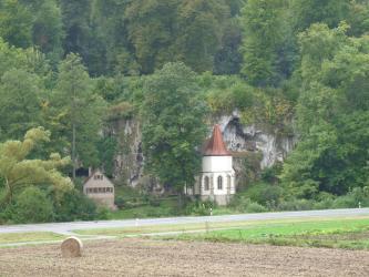 Hinter der Kapelle St. Wendel ragt eine grauweiße, zerfurchte Felswand empor. Teilweise ist das Gestein von dichtem Buschwerk überwuchert; rechts und links umrahmen es hohe Bäume. Rechts ist außerdem eine Höhle zu erkennen.