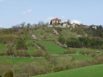 Auf der Kuppe eines nach oben hin steil ansteigenden grünen Hanges thront Schloss Stetten. Im oberen Bereich des Hanges sind sowohl längs- als auch abwärtslaufende Steinhügel zu erkennen. Auch Baum- und Waldstreifen durchziehen den Hang.