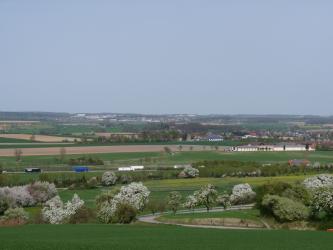 Das Bild zeigt eine nur wenig bewaldete, weite Ebene mit Grünland- und Ackerflächen. Im Vordergrund sind blühende Bäume und Straßen zu sehen, zum Horizont hin verteilen sich Industriegebiete und Siedlungen.