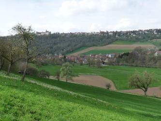 Der Blick geht über eine nach unten hin abfallende grüne Wiese über ein bewirtschaftetes Tal, an das sich ein wieder ansteigender, teils bewaldeter Hang anschließt. Im Mittelgrund sowie auf der Anhöhe liegen Ortschaften, hinten links auch ein Schloss..