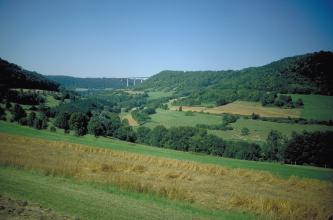 Das Bild zeigt ein weites, teilweise bewaldetes Tal mit Grün- und Ackerflächen. Von links nach rechts ziehen sich Höhenzüge entlang; auch sie bewaldet. Im Hintergrund verbindet eine Autobahnbrücke zwei der Höhen.