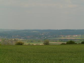 Hinter einer Grünlandfläche sieht man eine weite Hochebene, die zur Mitte hin leicht vertieft ist. Äcker und Wiesen wechseln sich ab mit Ortschaften und größerer Bewaldung im Hintergrund.