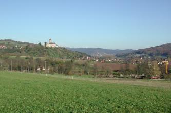 Hinter einer nach rechts abfallenden Grünfläche und einigen Bäumen erheben sich gewölbte Ackerflächen sowie nach links und rechts ansteigende, bewachsene Hänge. Auf der Kuppe des Hanges links ist zudem eine Burg erkennbar.
