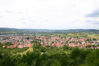 Von erhöhtem Standpunkt aus blickt man auf eine dicht besiedelte, im Vordergrund bewaldete Ebene. Im Hintergrund schließen sich begrünte Äcker, bewaldete Hänge sowie weitere Siedlungen an.