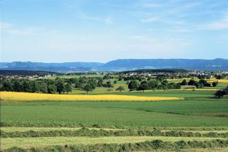 Blick in eine Landschaft. Im Vordergrund befinden sich vor vereinzelten Bäumen und Siedlungen begrünte Ackerflächen und ein gelbes Rapsfeld. Im Hintergrund erheben sich in der Ferne Bergrücken in den blauen Himmel.
