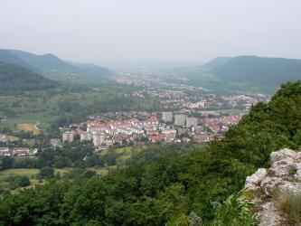 Von erhöhtem Standpunkt aus hat man - über Felsen und Baumwipfel - einen weiten Blick auf ein Tal und mehrere, fast zusammenhängende Ortschaften, die bis zum Horizont reichen. Links und rechts grenzen bewaldete Höhenzüge an.