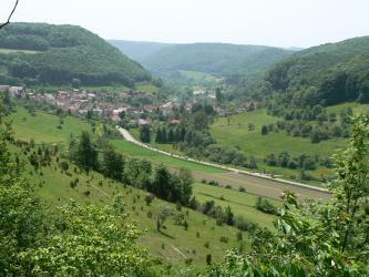 Von oben blickt man über steile, mit Hecken und Bäumen bewachsene Hänge auf ein überwiegend grünes Tal mit Viehweiden, aber auch Äckern. Links hinten, unter einem bewaldeten Hang, liegt eine Ortschaft. Mittig und rechts schließen sich weitere Hänge an.