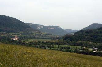 Über eine abschüssige Wiese blickt man auf ein eng wirkendes Tal mit Grün- und Nutzflächen (Fussballfeld). Steile bewaldete Hänge rechts und links geben den Blick zur Mitte frei, wo sich weitere, mit Felsen bestückte Anhöhen zeigen.
