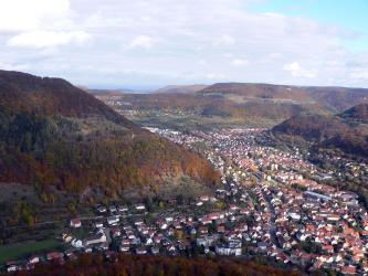 Aus großer Höhe blickt man auf mehrere, unterschiedlich hohe, teilweise bewaldete Hänge, die sich bis zum Horizont fortsetzen. Zu deren Füßen breitet sich eine größere Ortschaft aus.